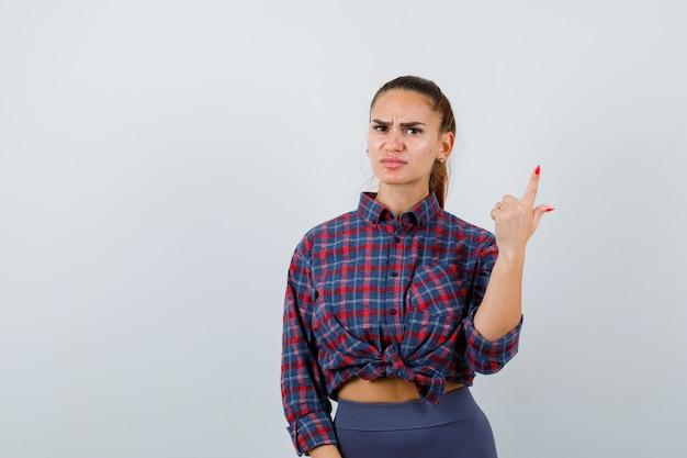 Jonge vrouw die omhoog wijst in een geruit hemd, broek en er serieus uitziet, vooraanzicht.