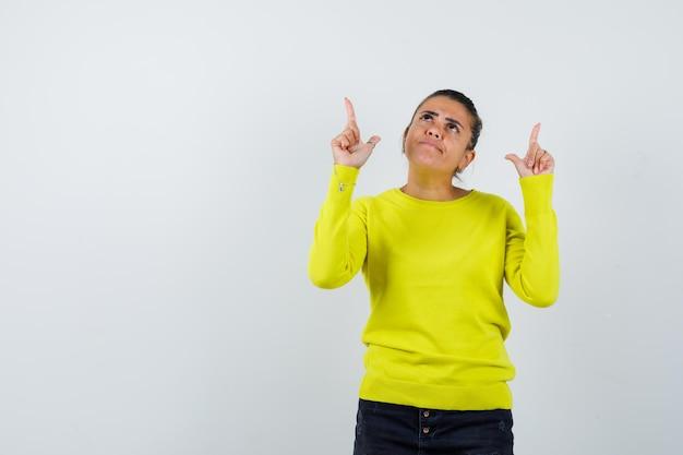 Jonge vrouw die omhoog wijst in gele trui en zwarte broek en er gelukkig uitziet