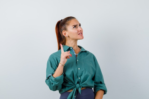 Jonge vrouw die omhoog wijst, omhoog kijkt in groen shirt en bezorgd kijkt, vooraanzicht.