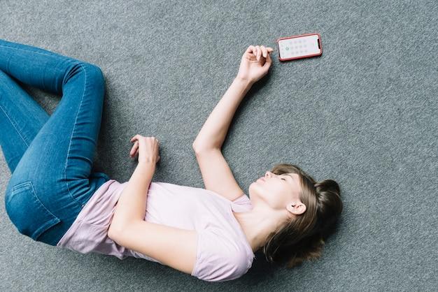 Jonge vrouw die onbewust op tapijt dichtbij slimme telefoon ligt