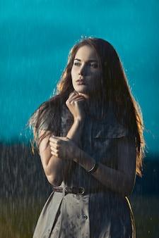 Jonge vrouw die onder regen bevriest