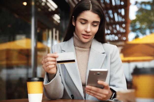 Jonge vrouw die online betaalt, met behulp van creditcard en mobiele telefoon zittend in een coffeeshop