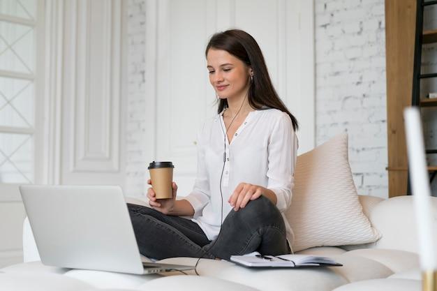 Jonge vrouw die online een zakelijke bijeenkomst heeft op haar laptop