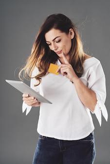 Jonge vrouw die online het winkelen doet