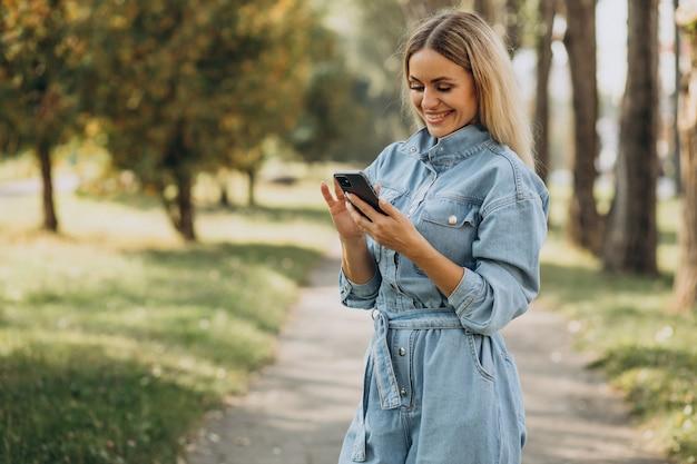 Jonge vrouw die online in park winkelt