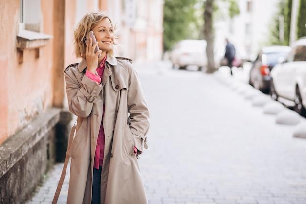 Jonge vrouw die online op telefoon winkelt