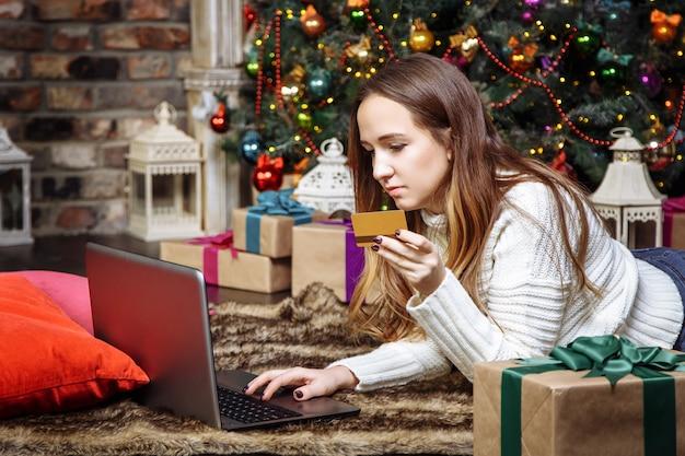 Jonge vrouw die online thuis het winkelen met creditcard en laptop doet. kerstinkopen concept