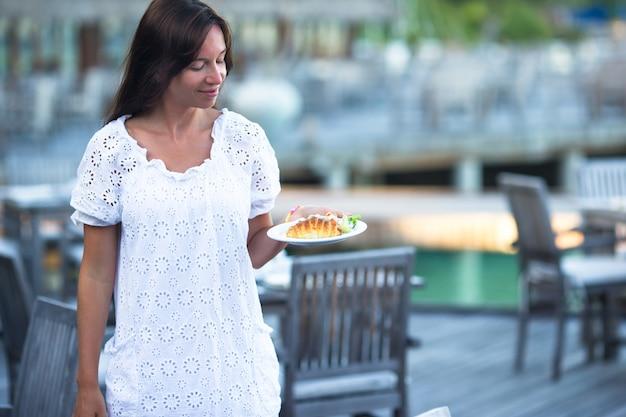 Jonge vrouw die ontbijt hebben bij openluchtkoffie op de zomervakantie
