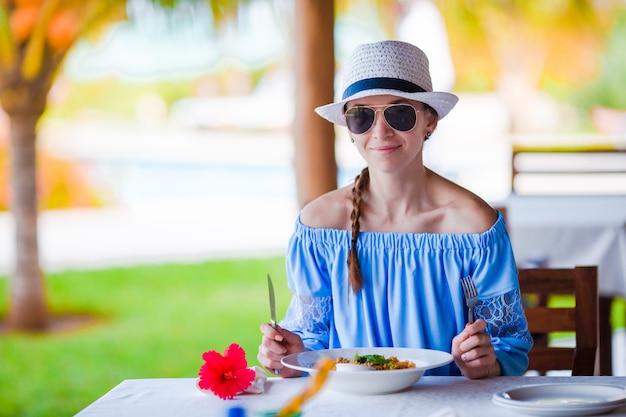 Jonge vrouw die ontbijt heeft bij openluchtkoffie op de zomervakantie