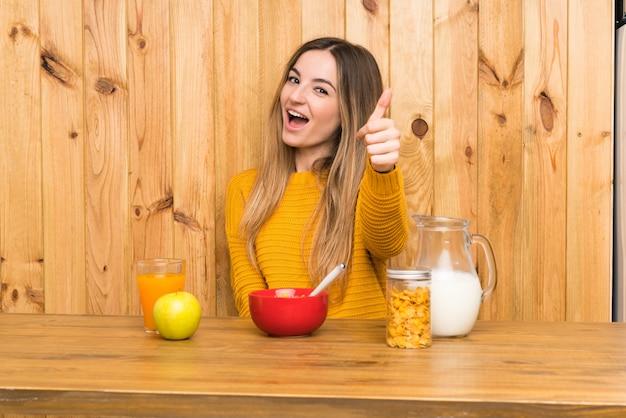 Jonge vrouw die ontbijt in een keuken met omhoog duimen heeft omdat er iets goeds is gebeurd