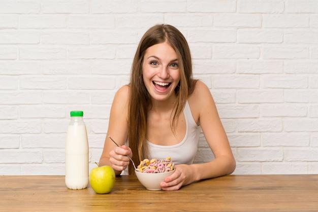 Jonge vrouw die ontbijt met kom graangewassen heeft