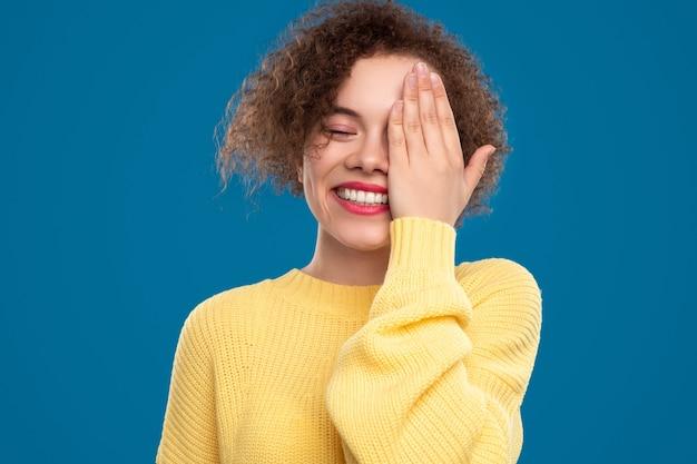 Jonge vrouw die oog behandelt met hand lachen