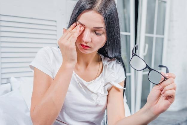 Jonge vrouw die oogglazen draagt wat betreft haar ogen met hand