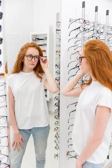 Jonge vrouw die oogglazen kiest en spiegel in optica bekijkt