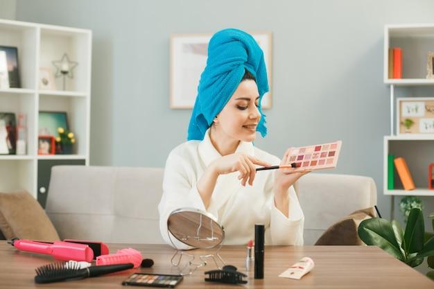 Jonge vrouw die oogschaduwpalet vasthoudt en bekijkt met make-upborstel gewikkeld haar in een handdoek zittend aan tafel met make-uptools in de woonkamer