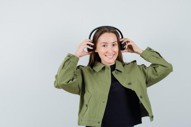 Jonge vrouw die oortelefoons in groen jasje draagt en heel, vooraanzicht kijkt.