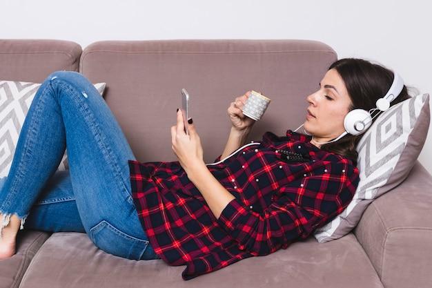 Jonge vrouw die op bank het luisteren muziek op hoofdtelefoon ligt