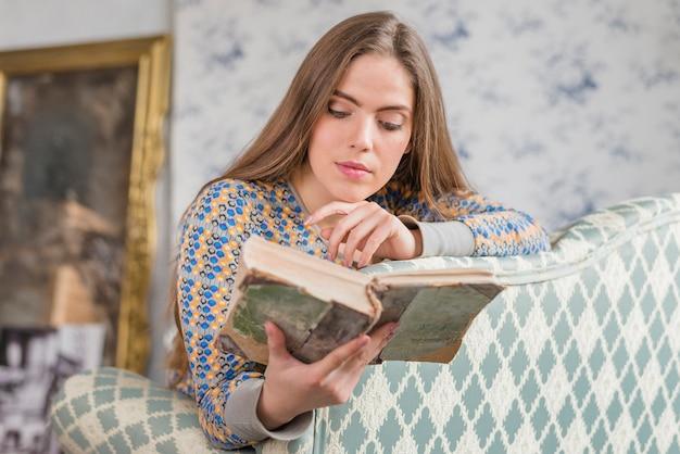 Jonge vrouw die op bank leunt die gescheurd uitstekend boek leest