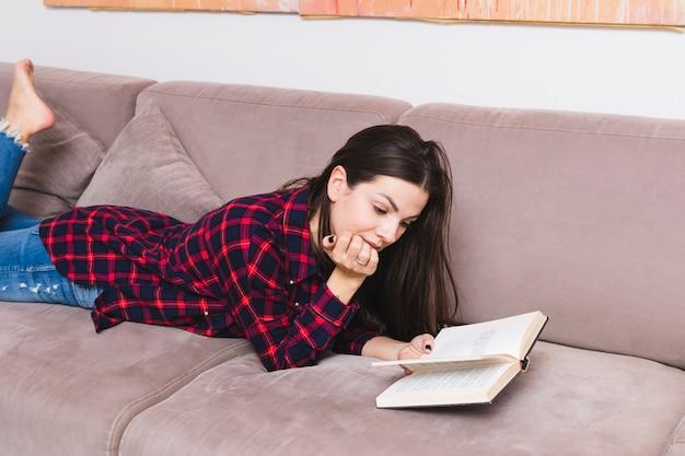 Jonge vrouw die op bank ligt die het boek leest