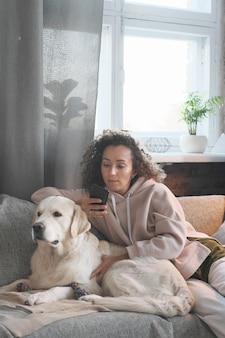 Jonge vrouw die op bank samen met haar hond rust en haar mobiele telefoon in de kamer gebruikt