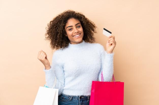 Jonge vrouw die op beige het winkelen van de muurholding zakken en een creditcard wordt geïsoleerd