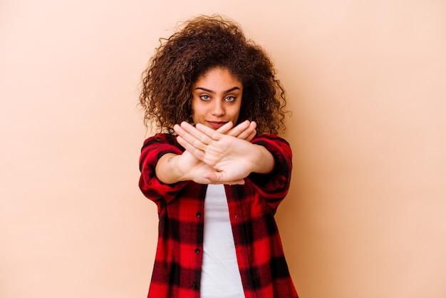 Jonge vrouw die op beige muur wordt geïsoleerd die een ontkenningsgebaar doet