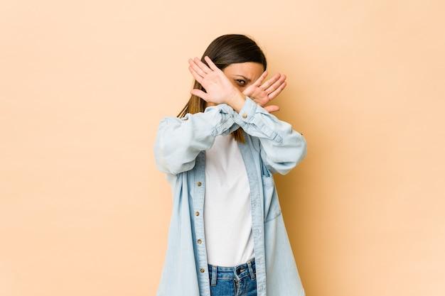 Jonge vrouw die op beige muur wordt geïsoleerd die twee gekruiste wapens houdt, ontkenningsconcept.