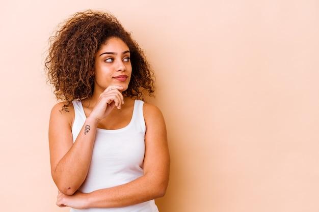 Jonge vrouw die op beige muur wordt geïsoleerd die zijwaarts met twijfelachtige en sceptische uitdrukking kijkt