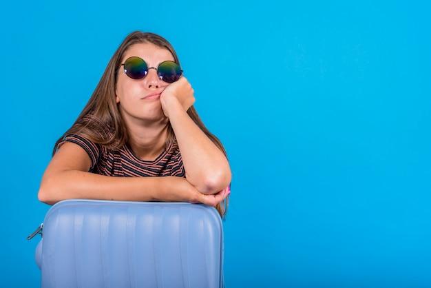 Jonge vrouw die op blauwe koffer leunt