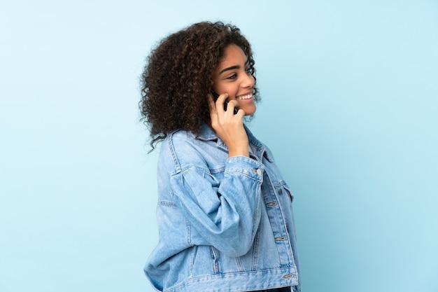 Jonge vrouw die op blauwe muur wordt geïsoleerd die een gesprek met de mobiele telefoon met iemand houdt