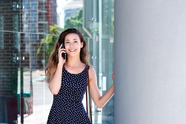 Jonge vrouw die op celtelefoon buiten spreekt