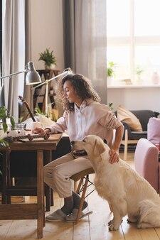 Jonge vrouw die op computer aan de tafel thuis werkt terwijl haar hond dichtbij haar zit