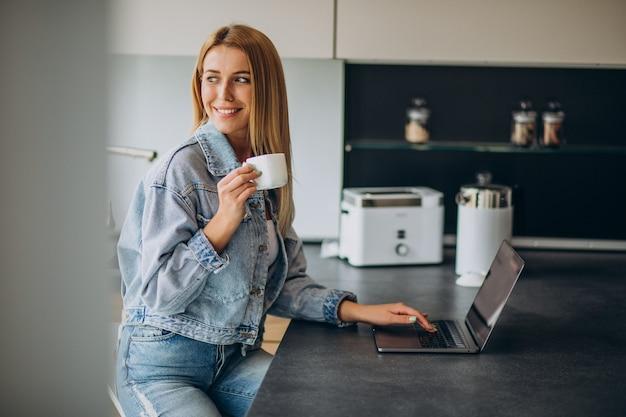 Jonge vrouw die op computer van huis werkt