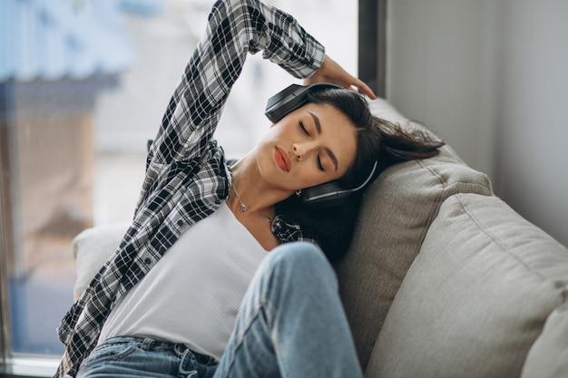 Jonge vrouw die op de bank in oortelefoons ligt die aan muziek luistert