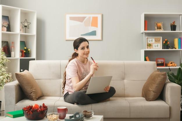 Jonge vrouw die op de bank zit achter de salontafel en een laptop vasthoudt in de woonkamer