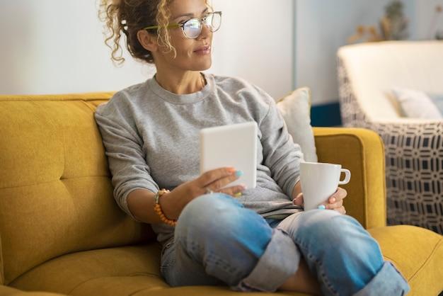 Jonge vrouw die op de bank zit terwijl ze een digitale tablet gebruikt en koffie drinkt nadenkende vrouw
