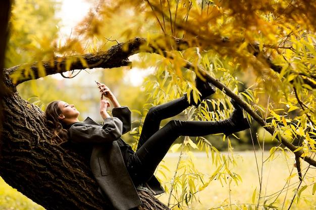 Jonge vrouw die op de boom met mobiele telefoon rust