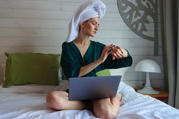 Jonge vrouw die op de computer werkt na een douche