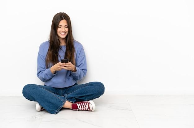 Jonge vrouw die op de grond zit en een bericht verzendt met de mobiel