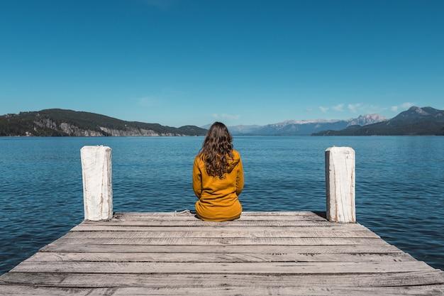 Jonge vrouw die op de ligplaats in de buurt van de rivier zit en aan de kust kijkt