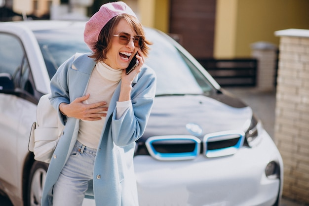 Jonge vrouw die op de telefoon door haar elektrische auto spreekt