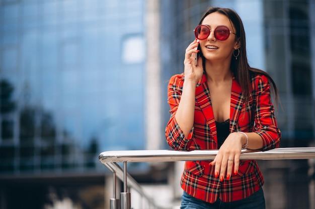 Jonge vrouw die op de telefoon door het bureaucentrum spreekt