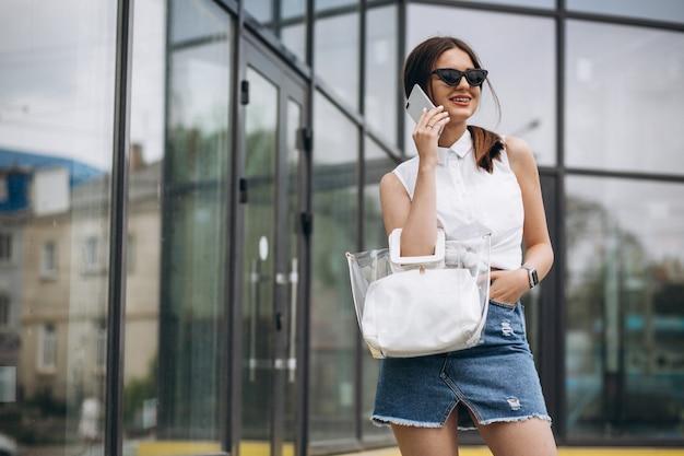 Jonge vrouw die op de telefoon in het stadscentrum spreekt