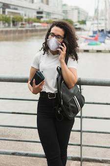 Jonge vrouw die op de telefoon in openlucht spreekt