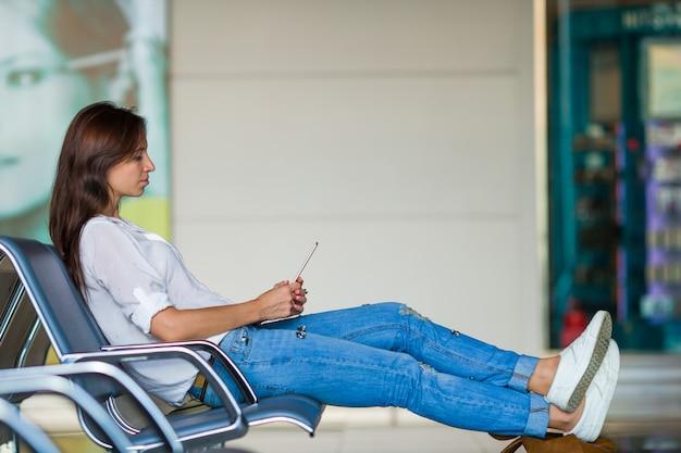 Jonge vrouw die op de telefoon spreekt terwijl het wachten instappen