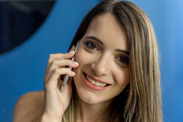 Jonge vrouw die op de telefoon spreekt