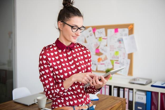 Jonge vrouw die op digitale tablet op kantoor werkt