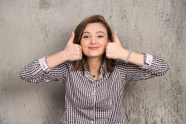 Jonge vrouw die op donkere muur wordt geïsoleerd die duimen met twee handen toont
