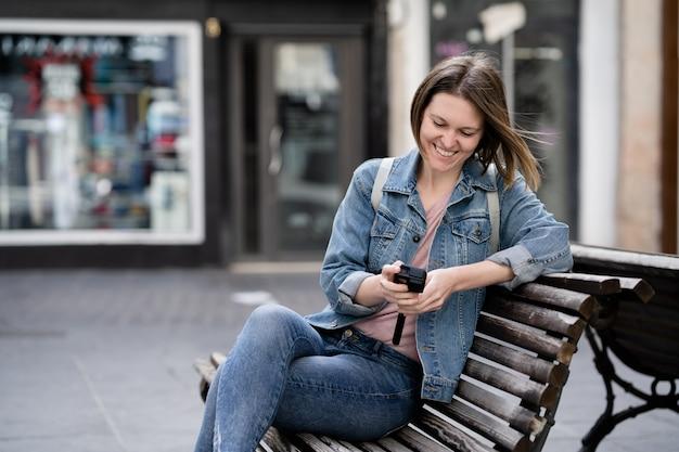 Jonge vrouw die op een bankje op straat zit te kijken naar de video's en foto's