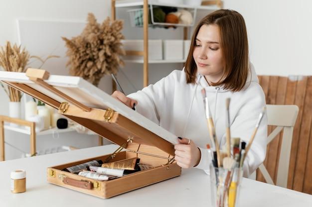 Jonge vrouw die op een canvas trekt